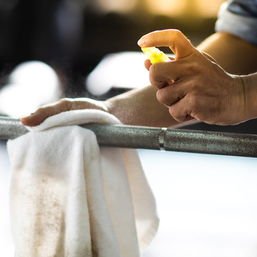 a person sanitizing fitness equipment
