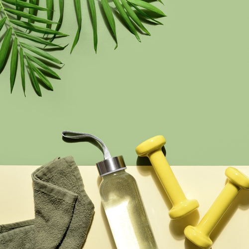 towel, water, dumbbells, and shoes on green background