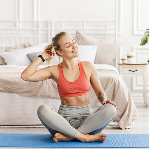 a woman sitting on a yoga mat and smiling