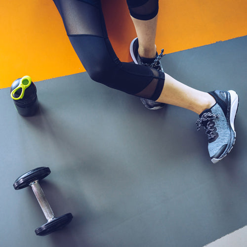 a person sitting on the floor with a dumbbell