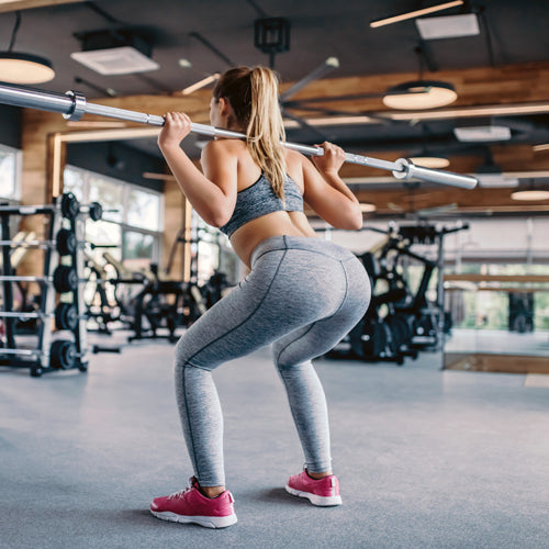 woman squatting with Olympic Bar