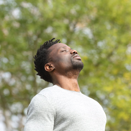 a man breathing in nature to reduce stress