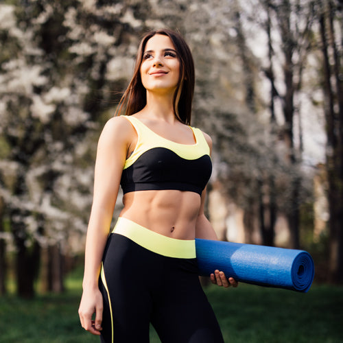 a smiling woman holding a yoga mat