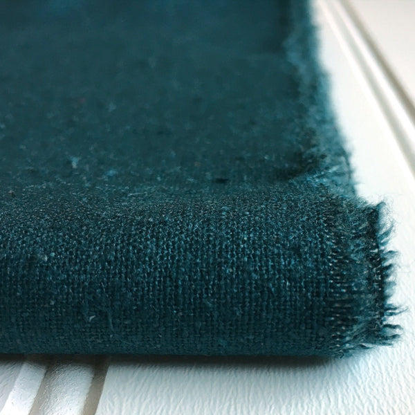 close-up of folded teal green raw silk noil