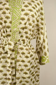 Cotton voile kimono robe dressing gown in cream with a small geometric fan block print pattern and green and cream trim, close up showing pockets.