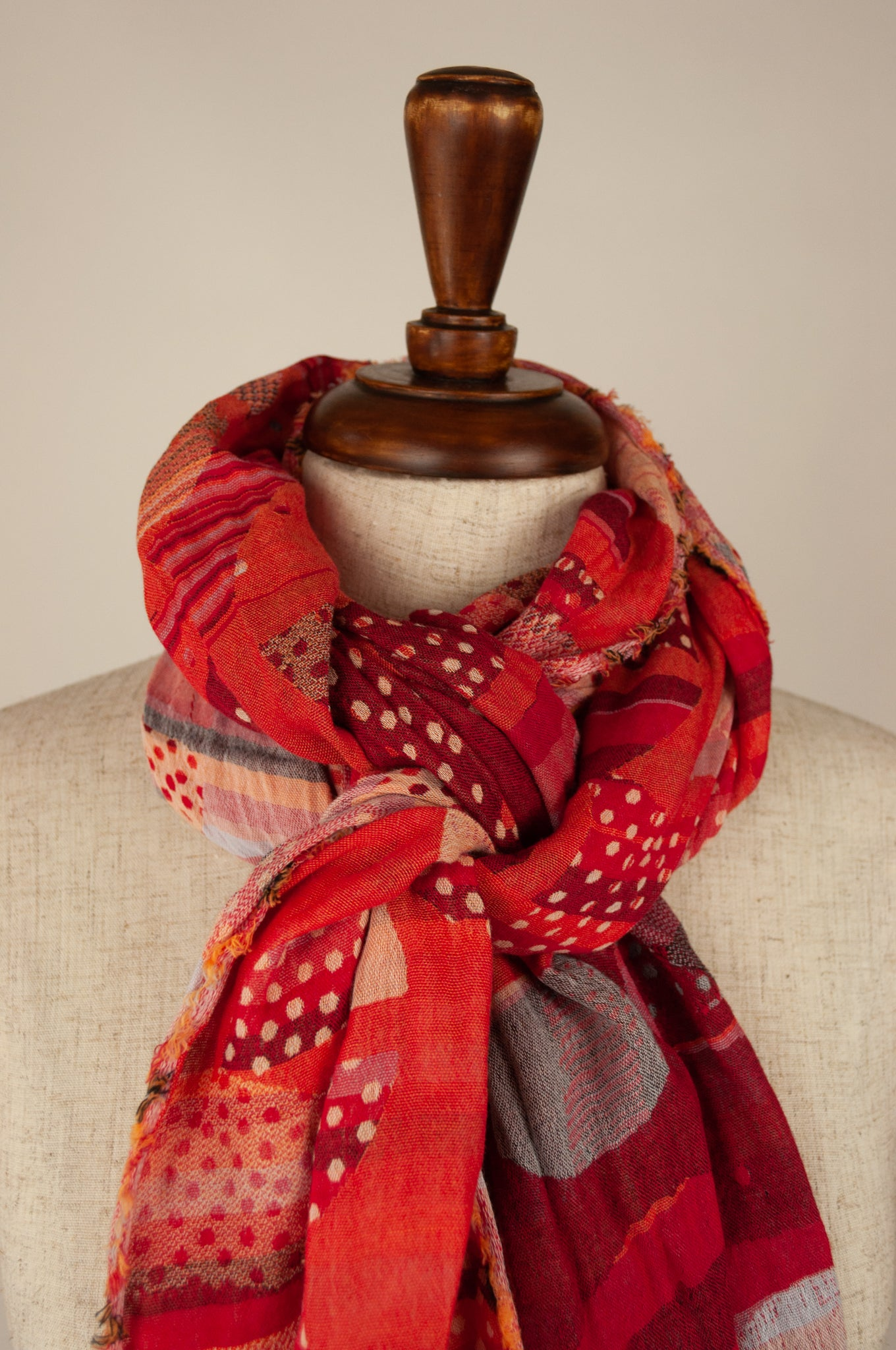 Létol French organic cotton scarf with a geometric print of circles and stripes in tones of coral, orange and red.