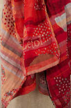 Load image into Gallery viewer, Létol French organic cotton scarf with a geometric print of circles and stripes in tones of coral, orange and red.