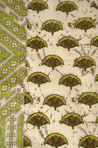 Cotton voile kimono robe dressing gown in cream with a small geometric fan block print pattern and green trim, close up of fabric.