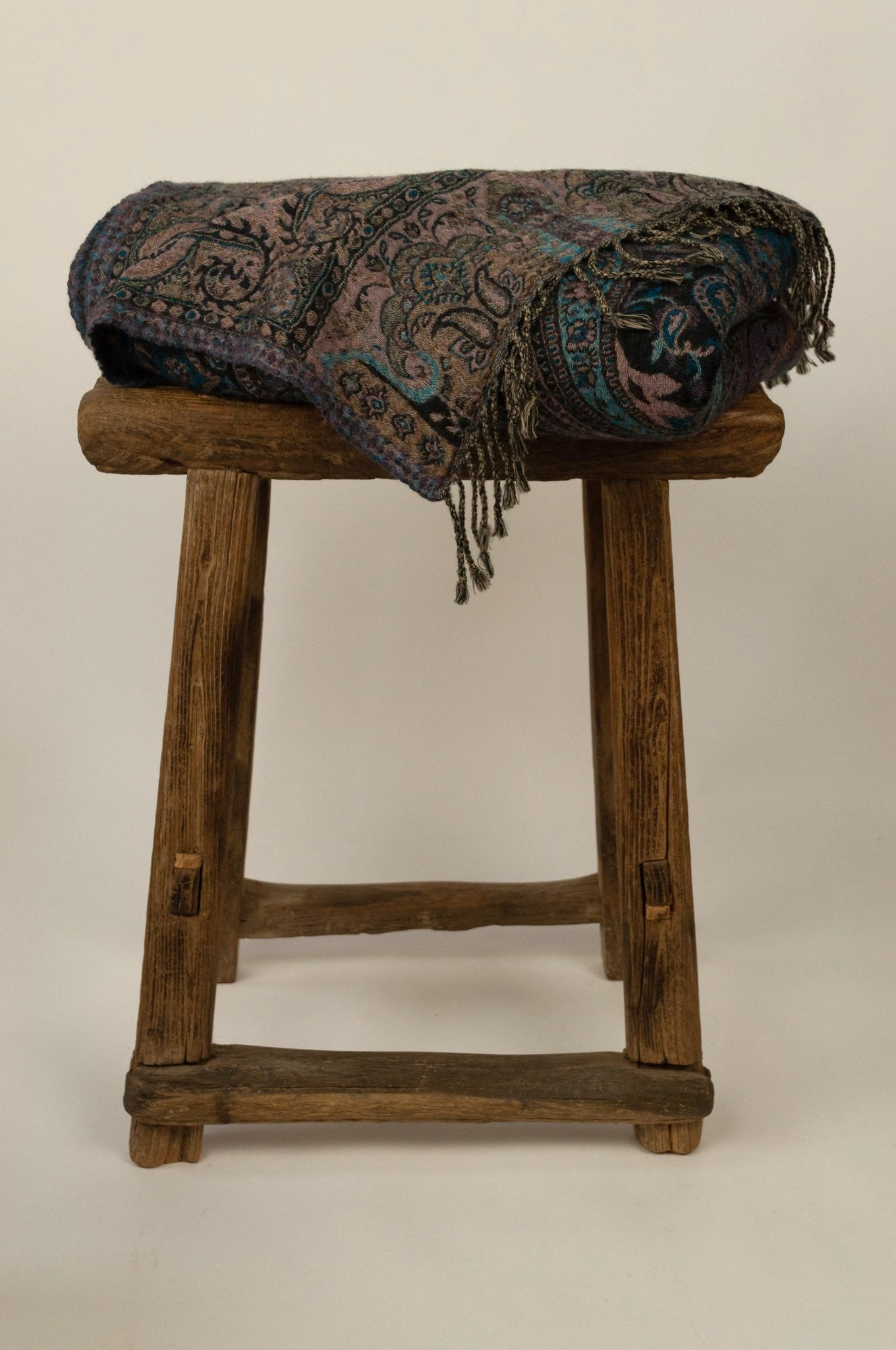 Juniper Hearth pure wool reversible tasseled throw is a classic paisley design in shades of blue and teal, with a soft mauve ground on the reverse.
