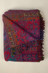 Juniper Hearth pure wool reversible tasseled throw has a classic paisley design in striking shades of purple and azure blue with a stunning magenta, red and orange reverse.