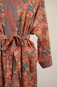 Cotton voile kimono robe dressing gown in a rust red palm print with red and blue matching geometric trim, close up showing pockets.