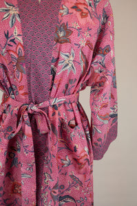 Cotton voile kimono robe dressing gown in a pink floral print and pink and blue geometric trim, close up showing pockets.