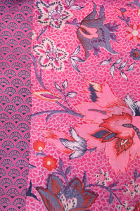 Cotton voile kimono robe dressing gown in a pink floral print and pink and blue geometric trim, fabric close up.
