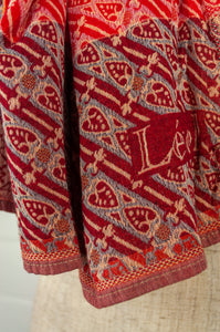 Létol French organic cotton scarf, patterned in shades of red with grey accents.