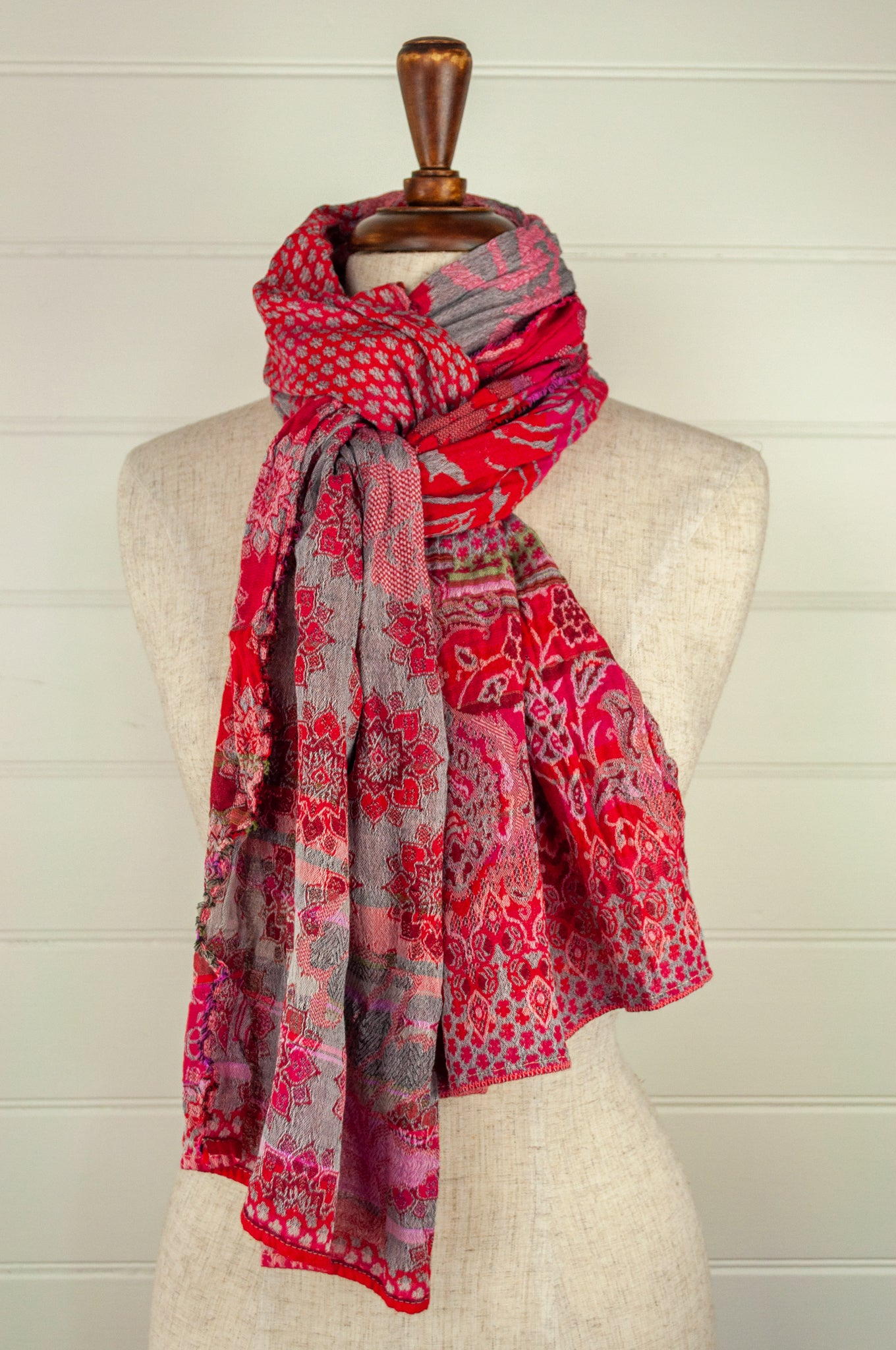 Létol French organic cotton scarf, patterned in shades of rose pink and red on a silver grey background, with lime highlights.