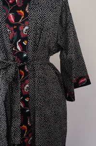 Cotton voile kimono robe dressing gown in simple white on black print, with contrast floral trim, close up.