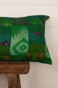 Vintage silk patchwork kantha bolster cushion, 30cmx60cm, in shades of emerald green, with ikat pieces and highlights of royal purple. Close up.