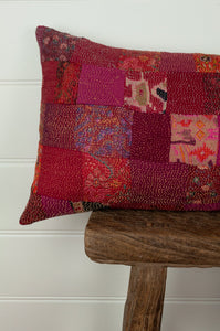 Vintage silk kantha bolster cushion, 30cmx60cm, in rich and rosy tones of red and pink. Close up.