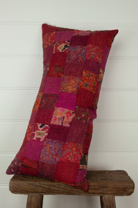 Vintage silk kantha bolster cushion, 30cmx60cm, in rich and rosy tones of red and pink.