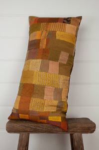 Vintage silk patchwork kantha bolster cushion, 30cmx60cm, is in spicy shades of mustard, gold, turmeric and olive.