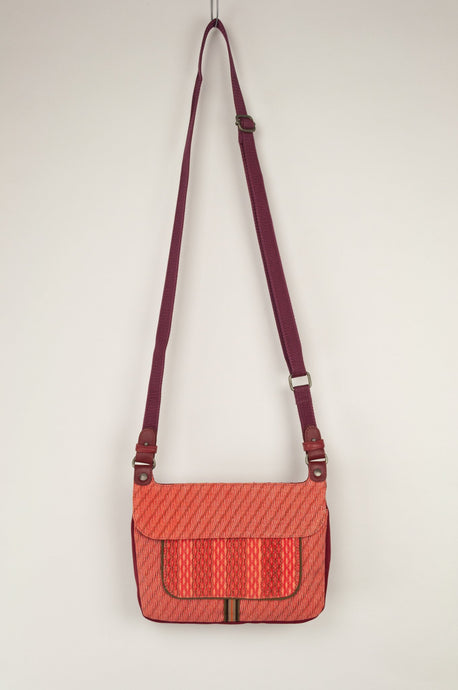 Anna Kaszer Nigi mini crossbody bag in tango (red and orange pattern with burgundy back), with adjustable shoulder strap.