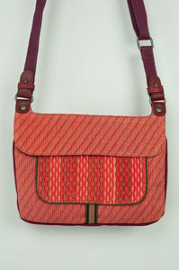 Anna Kaszer Nigi mini crossbody bag in tango (red and orange pattern with burgundy back), with adjustable shoulder strap. Close up.