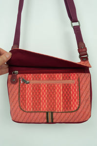 Anna Kaszer Nigi mini crossbody bag in tango (red and orange pattern with burgundy back), with adjustable shoulder strap. Showing zips and openings.