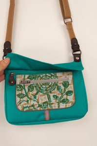 Anna Kaszer Nigi mini crossbody bag in nolana (floral pattern panel on turquoise), with adjustable shoulder strap. Showing zips and opening.