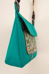 Anna Kaszer Nigi mini crossbody bag in nolana (floral pattern panel on turquoise), with adjustable shoulder strap. Side view.