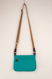 Anna Kaszer Nigi mini crossbody bag in nolana (floral pattern panel on turquoise), with adjustable shoulder strap. Rear view.