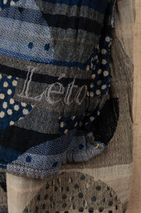 Létol French organic cotton scarf with a geometric design of stripes and overlaid dotted circles, in deep tones of indigo, navy blue, silver and charcoal (close up).