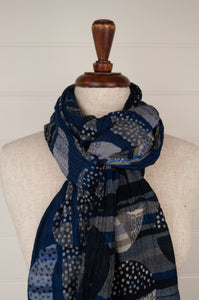 Létol French organic cotton scarf with a geometric design of stripes and overlaid dotted circles, in deep tones of indigo, navy blue, silver and charcoal.