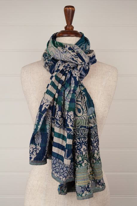 Létol French organic cotton scarf with a bold stripe and floral design in deep shades of turquoise, teal and cobalt blue, with yellow highlights on an oatmeal background.