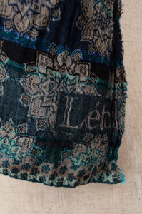 Létol French organic cotton scarf with a geometric and floral design in deep shades of turquoise, teal and cobalt blue (close up).
