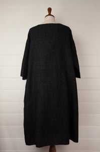 Dve 100% charcoal boiled wool, one size Padma dress, embroidered detail at gathered front waist panel, pockets and three quarter sleeves (rear view).