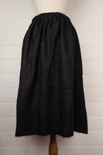 Load image into Gallery viewer, Dve Isha one size skirt in charcoal wool, elastic waist at back, adjustable tie at waist, side pockets (rear view).