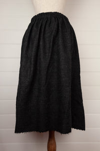 Dve Isha one size skirt in charcoal wool, elastic waist at back, adjustable tie at waist, side pockets (rear view).