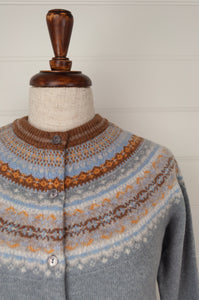 Made in Scotland, Eribé pure wool fairisle short cropped cardigan in Mirage, soft grey blue with patterned yoke and trim in shades of toffee brown, gold yellow, ecru and sky blue.