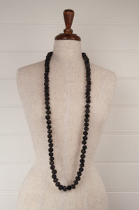 This beautiful necklace is made from wool/silk fabric remnants, each bead formed by hand, filled with smaller pieces of fabric and thread, in black with white highlights.