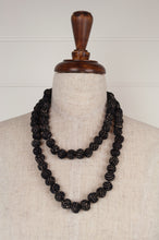 Load image into Gallery viewer, This beautiful necklace is made from wool/silk fabric remnants, each bead formed by hand, filled with smaller pieces of fabric and thread, in black with white highlights.