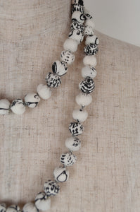 This beautiful necklace is made from pure cotton fabric remnants, each bead formed by hand, filled with smaller pieces of fabric and thread, in white with black highlights.