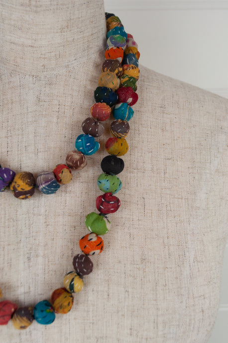 Handmade fabric necklace from Yavi, India, constructed from brightly coloured fabric remnants, kantha stitched.