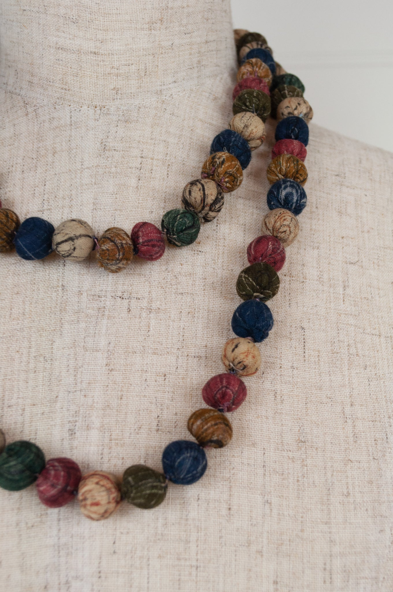 This beautiful necklace is made from handpainted fabric remnants, each bead formed by hand, filled with smaller pieces of fabric and thread, in earthy tones.