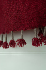 Baby yak wool handwoven tasseled throw rug in cherry red ombre fading to natural. (close up)
