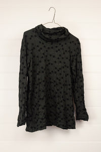 Valia dotted high neck, black spots on deep olive, long sleeve t-shirt in merino wool jacquard..