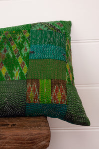 Vintage silk patchwork kantha bolster cushion, 30cmx60cm, in shades of emerald green, with ikat pieces and highlights of royal purple (detail).
