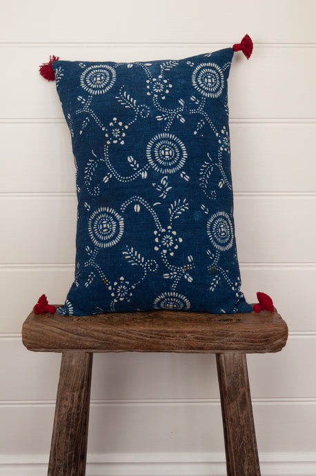 Vintage indigo blue and white cotton small 30x45cm bolster cushion with red tassels.