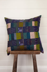 Vintage silk kantha square patchwork cushion in ecru, olive green and teal, with patches of navy ikat.