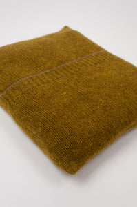 Juniper Hearth baby yak wool poncho in Weed, a deep yellow olive green shade (close up in pouch).