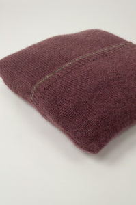 Juniper Hearth baby yak wool poncho in light plum, folded in pouch.
